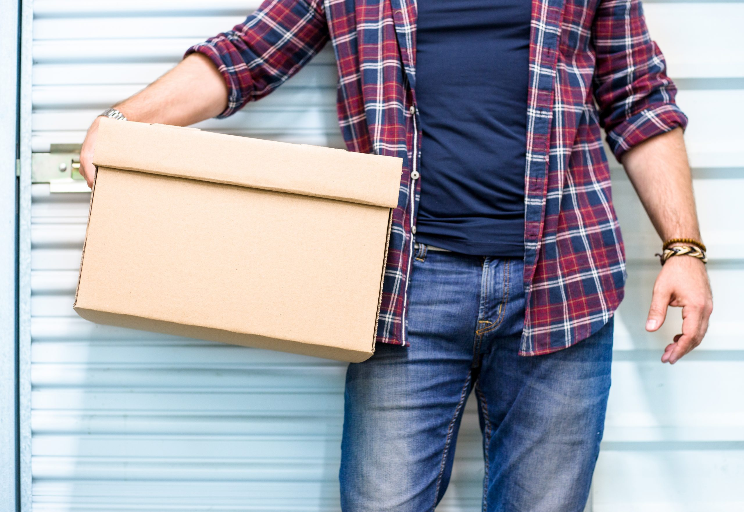 man holding box in front of self storage unit