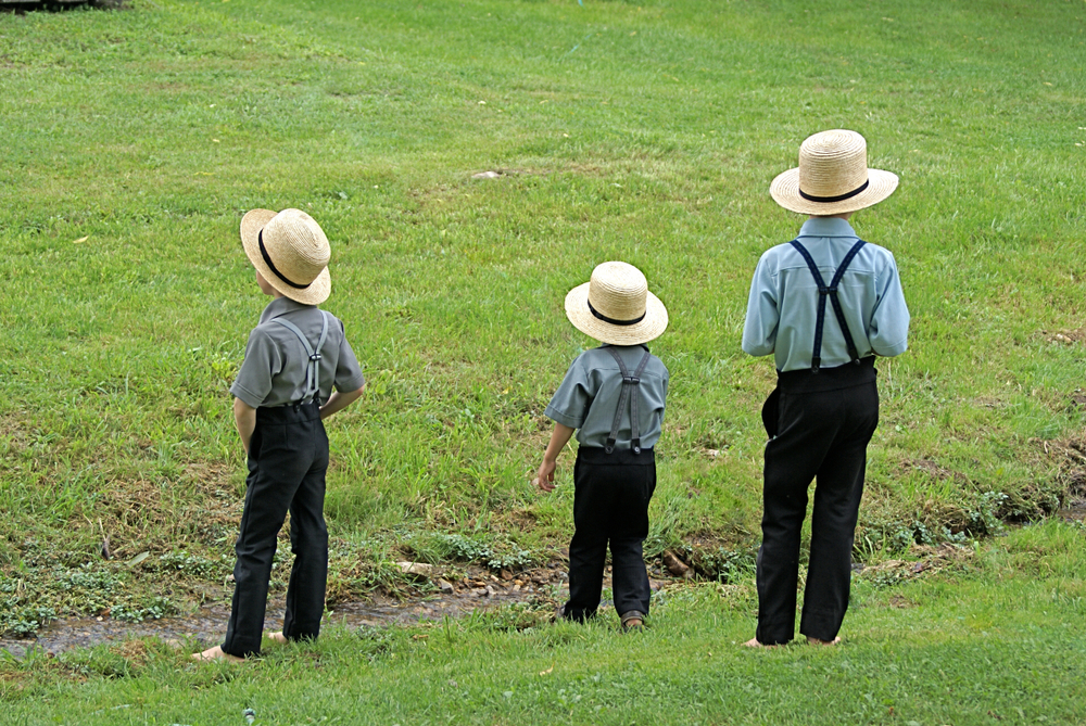 amish boys by a stream having fun living in lancaster, pa